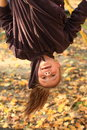 Smiling hanging girl kid with head down and flying hair in ponytail Royalty Free Stock Image
