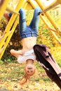 Smiling hanging girl kid with head down and flying hair in ponytail on kids playground Stock Photo