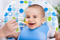 Smiling happy adorable baby eating fruit mash in the kitchen Royalty Free Stock Photo