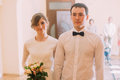 Smiling happy bride with wedding bouquet and groom standing holding hands in hotel or registry office Royalty Free Stock Photo
