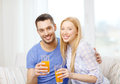 Smiling happy couple at home drinking juice love family healthy food and happiness concept Stock Photography