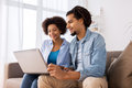 Smiling happy couple with laptop at home Royalty Free Stock Photo