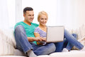 Smiling happy couple with laptop at home love family technology internet and happiness concept witl computer Stock Photo