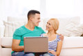 Smiling happy couple with laptop at home love family technology internet and happiness concept witl computer Stock Image