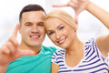 Smiling happy couple making frame gesture at home love family and happiness concept Royalty Free Stock Photos