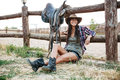 Smiling happy cowgirl sitting and resting at the ranch fence Royalty Free Stock Photo