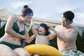 Smiling happy family helping son put on goggles by the poolside Royalty Free Stock Photo