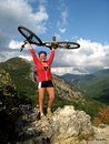 Smiling happy girl with bike in the mountains