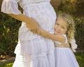 Smiling happy little girl with pregnant mother a very blue eyed blond hair flower at a wedding wearing a white dress holds on to Stock Images