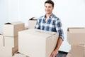 Smiling happy man carrying carton boxes at new flat Royalty Free Stock Photo