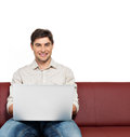 Smiling happy man with laptop sits on the divan Royalty Free Stock Photo