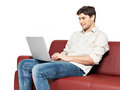 Smiling happy man with laptop sits on the divan portrait of isolated white Stock Photos