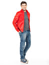 Smiling happy man in red jacket blue jeans and gymshoes full portrait of handsome beautiful guy standing isolated on white Royalty Free Stock Image