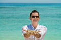 Smiling happy man on sandy beach in sunglasses hold a sand with blue sea background Royalty Free Stock Photo
