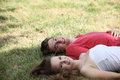 Smiling happy teenage couple relaxing on grass lying side by side their backs in the shade of a tree looking up at the camera Royalty Free Stock Photo