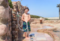 Smiling happy young boy rinsing off with a hose hosepipe to remove beach sand from his skin and shoes after relaxing on resort Royalty Free Stock Photos