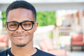 Smiling headshot closeup portrait of fine young man with big glasses undergrad student isolated on outside outdoors background Stock Photo