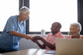 Smiling healthcare worker serving coffee to senior man sitting by friend Royalty Free Stock Photo