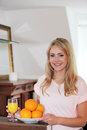 Smiling healthy woman with fresh oranges young a bowl of and a glass of freshly squeezed juice in her hand standing in her house Stock Image