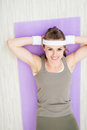 Smiling healthy woman laying on fitness mat