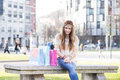 Smiling hippie girl with shopping bags in the street woman sitting on bench Stock Image