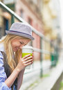 Smiling hipster girl with cup of hot beverage on city street in hat Stock Images