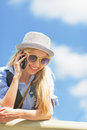Smiling hipster girl talking mobile phone against sky Royalty Free Stock Photo
