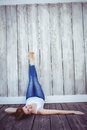 Smiling hipster woman with her legs against the wall outstretched a wooden background Royalty Free Stock Images