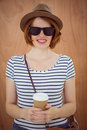 smiling hipster woman holding a take away coffee cup
