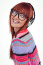 Smiling hipster woman listening music with headphones against white background Royalty Free Stock Images