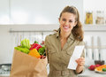 Smiling housewife with check and shopping bag full of vegetables young Stock Image