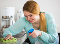 Smiling housewife cleaning up in domestic kitchen