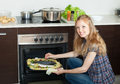 Smiling housewife cooking saltwater fish and potatoes on sheet p pan in oven at kitchen Royalty Free Stock Photography