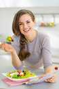 Smiling housewife eating fresh salad and reading magazine young in kitchen Stock Image