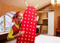 Smiling housewife with ironing board happy in room Royalty Free Stock Photography