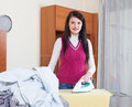 Smiling housewife ironing with iron at home Stock Image