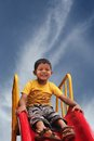 Smiling indian kid having fun playing in slider Stock Image