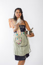 Smiling indian woman tosses flour an in an apron from a mixing bowl Royalty Free Stock Photography