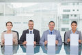 Smiling interview panel holding white paper in bright office sheets Stock Photography