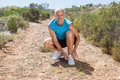 Smiling jogger tying his shoelace on mountain trail Royalty Free Stock Photo