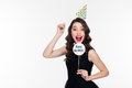 Smiling joyful pretty curly woman posing with birthday props isolated