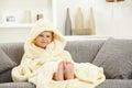 Smiling kid in bathrobe at home sofa bare feet Royalty Free Stock Photo