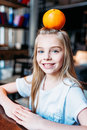 Smiling kid girl with orange on head sitting at home and looking at camera Royalty Free Stock Photo