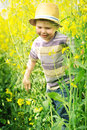 Smiling kid running among the canola flowers child Royalty Free Stock Images