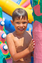 Smiling kid at a water park near the inflatable slides Stock Image