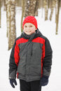 Smiling kid in winter forest wearing red hat and gray jacket standing Stock Images