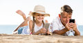 Smiling kids on beach with phone in hands Royalty Free Stock Photo