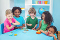 Smiling kids playing with modelling clay at their desk Royalty Free Stock Photos