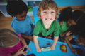 Smiling kids playing with modelling clay at their desk Royalty Free Stock Photography