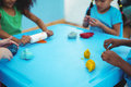 Smiling kids using modelling clay at their desk Stock Image
